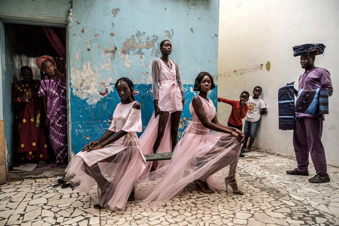 "Finbarr O'Reilly, ""Dakar Fashion"" (2018): Diarra Ndiaye, Ndeye Fatou Mbaye y Mariza Sakho visten trajes de la diseñadora Adama Paris, en el barrio de Medina en la capital senegalesa, Dakar, mientras los curiosos residentes observan. Imagen: © Finbarr O'Reilly"