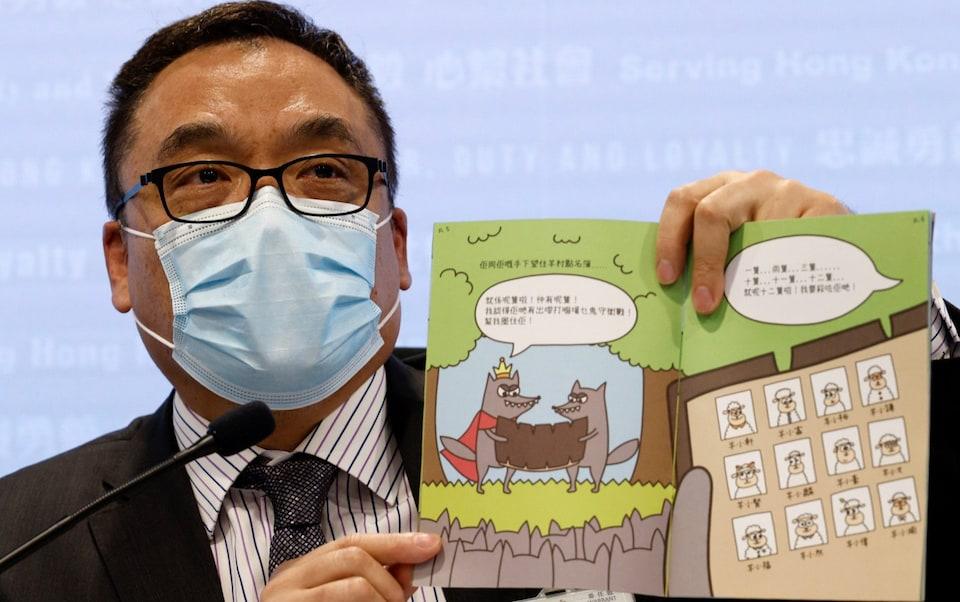 El superintendente principal de Hong Kong, Steve Li, sosteniendo uno de los libros. Fotografía: Reuters